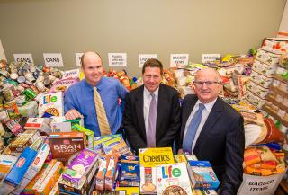 Chairman Jay Clayton and the Office of Public Affairs' Kevin Callahan (left) and John Nester are surrounded by a mountain of meals – 6 tons, total – in the bountiful Feds Feed Families collection room.